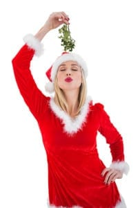 A blonde in a red festive dress puckering her lips and holding up mistletoe