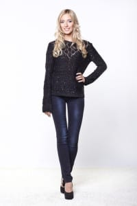 An attractive blonde woman in jeans and a sweater