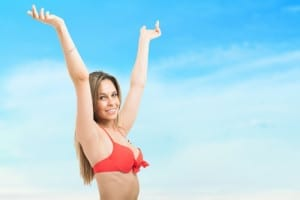 A beautiful woman from the waist up with her arms in the air in a red swimsuit top on a sky background
