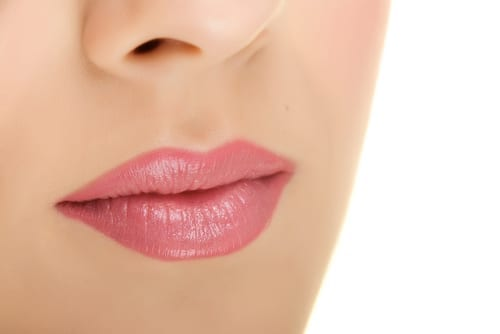 Closeup of a woman's pink lips with a beautiful soft skin.