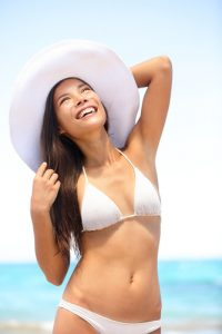 Sexy happy young woman at the beach wearing white sun hat and bikini bathing suit at the tropical ocean