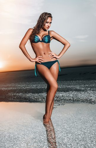 beautiful woman in a bathing suit standing on the beach at sunset-img-blog