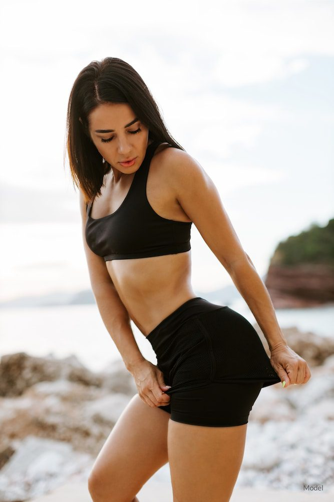 Woman on beach in black sports wear pulling at the material over her buttocks.