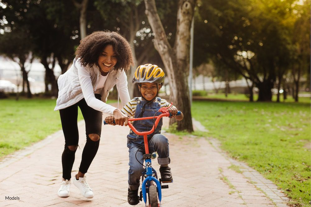 Women being active with her young son riding a bike.